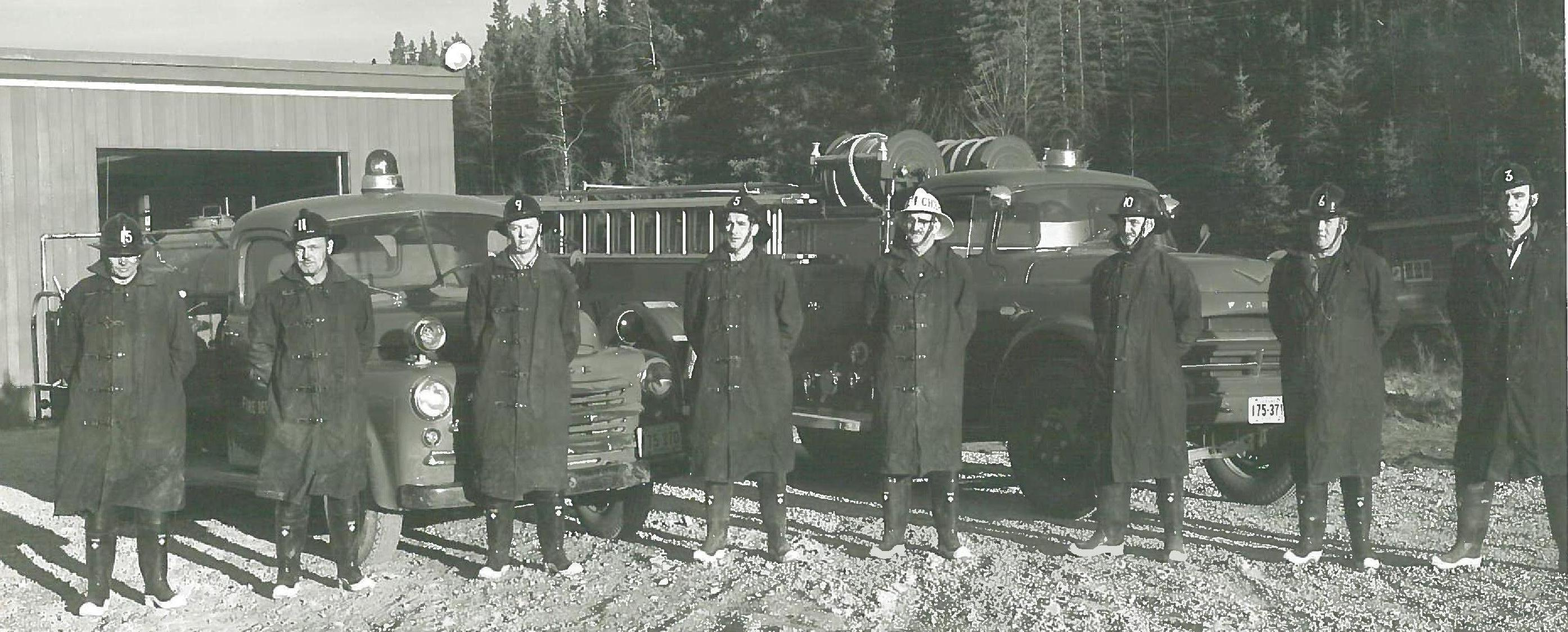 Old historical photo of 8 firefighters in front of some old fire trucks.