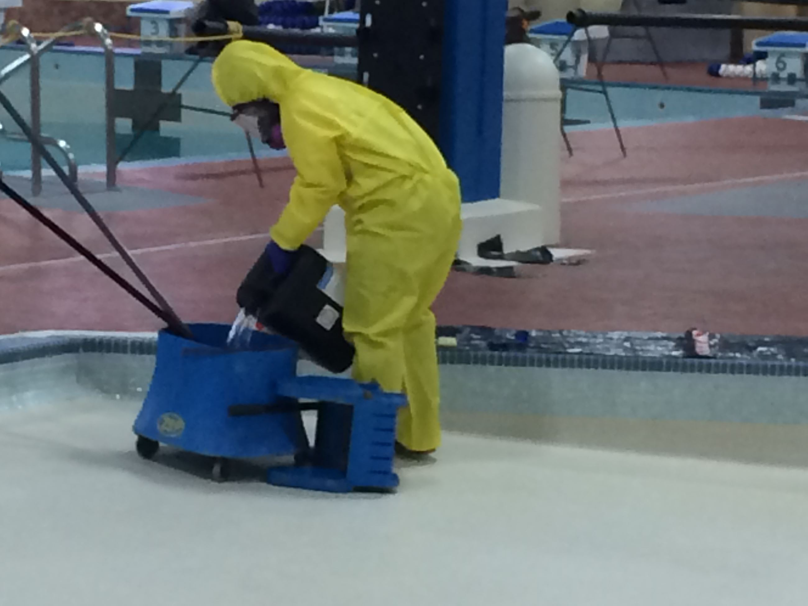 Lifeguard(s) prepare acid solution to de-scale the pool bottoms.