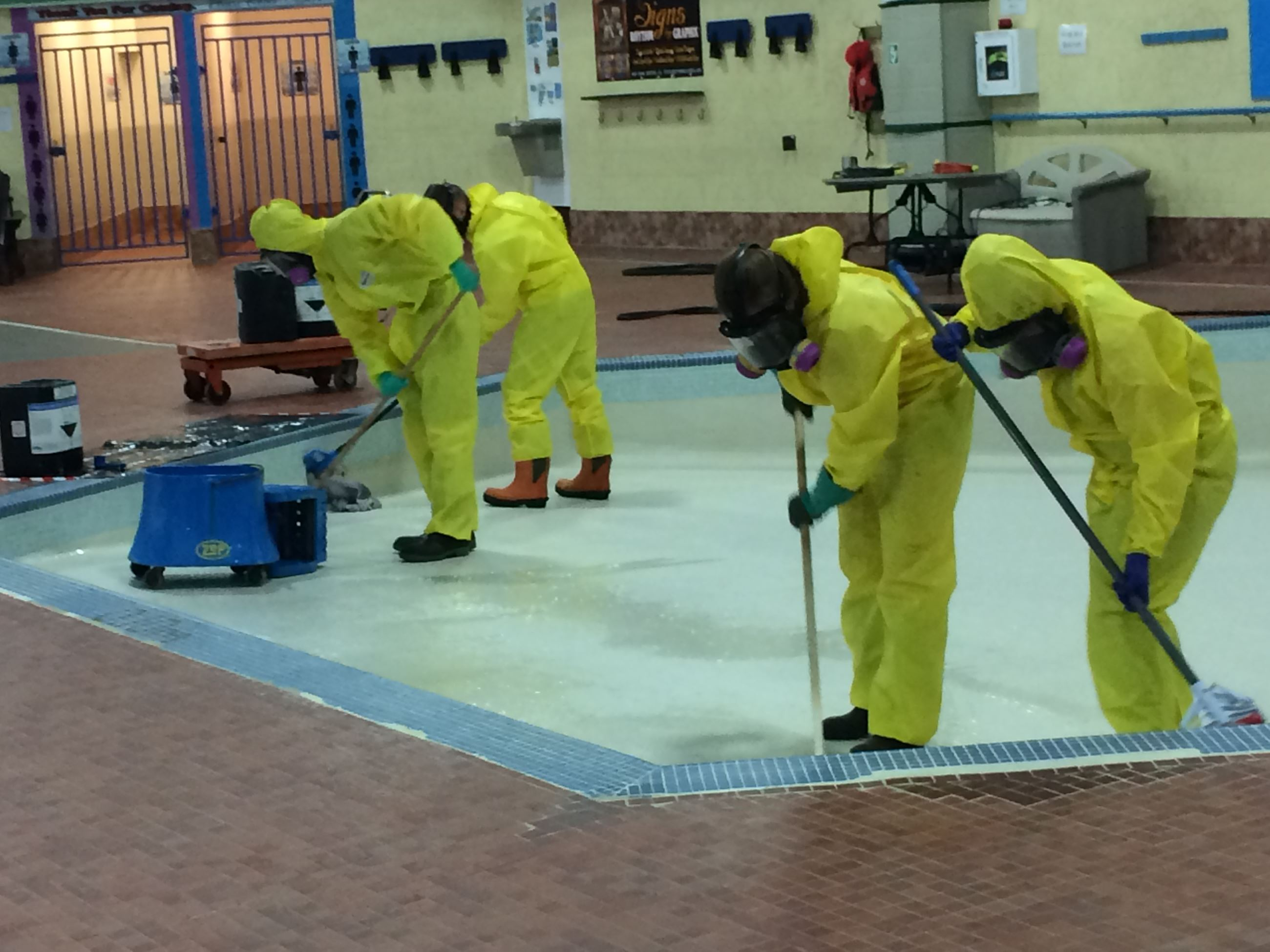 Two lifeguards spread the acid solution as two others scrub to remove scale.