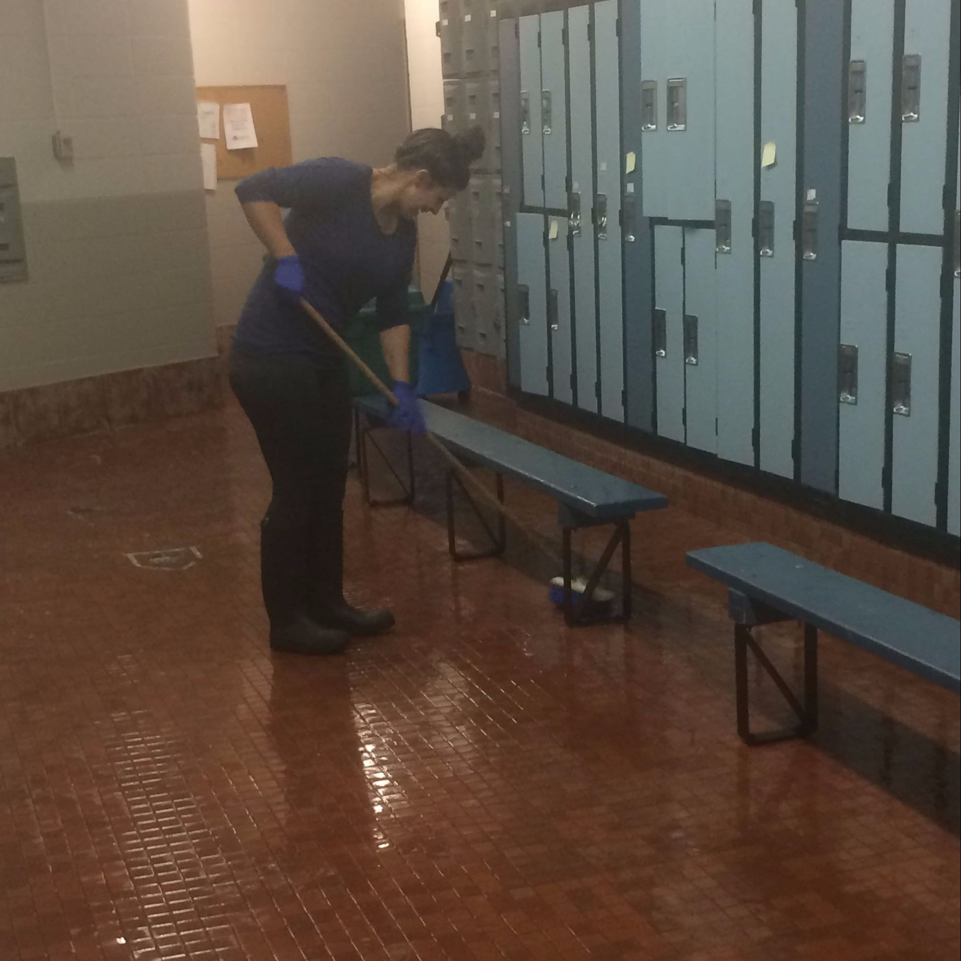 lifeguard preps the change room floor surfaces to buff off hard water stains and calcium build up.
