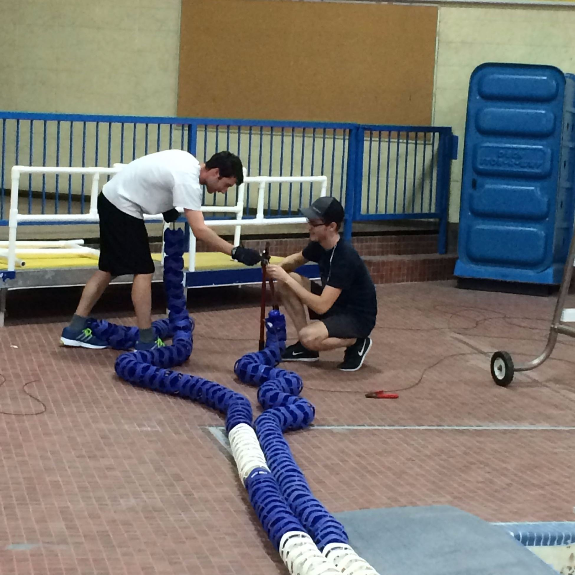 Lifeguards restring and crimp lane ropes in preparation for fall programming.